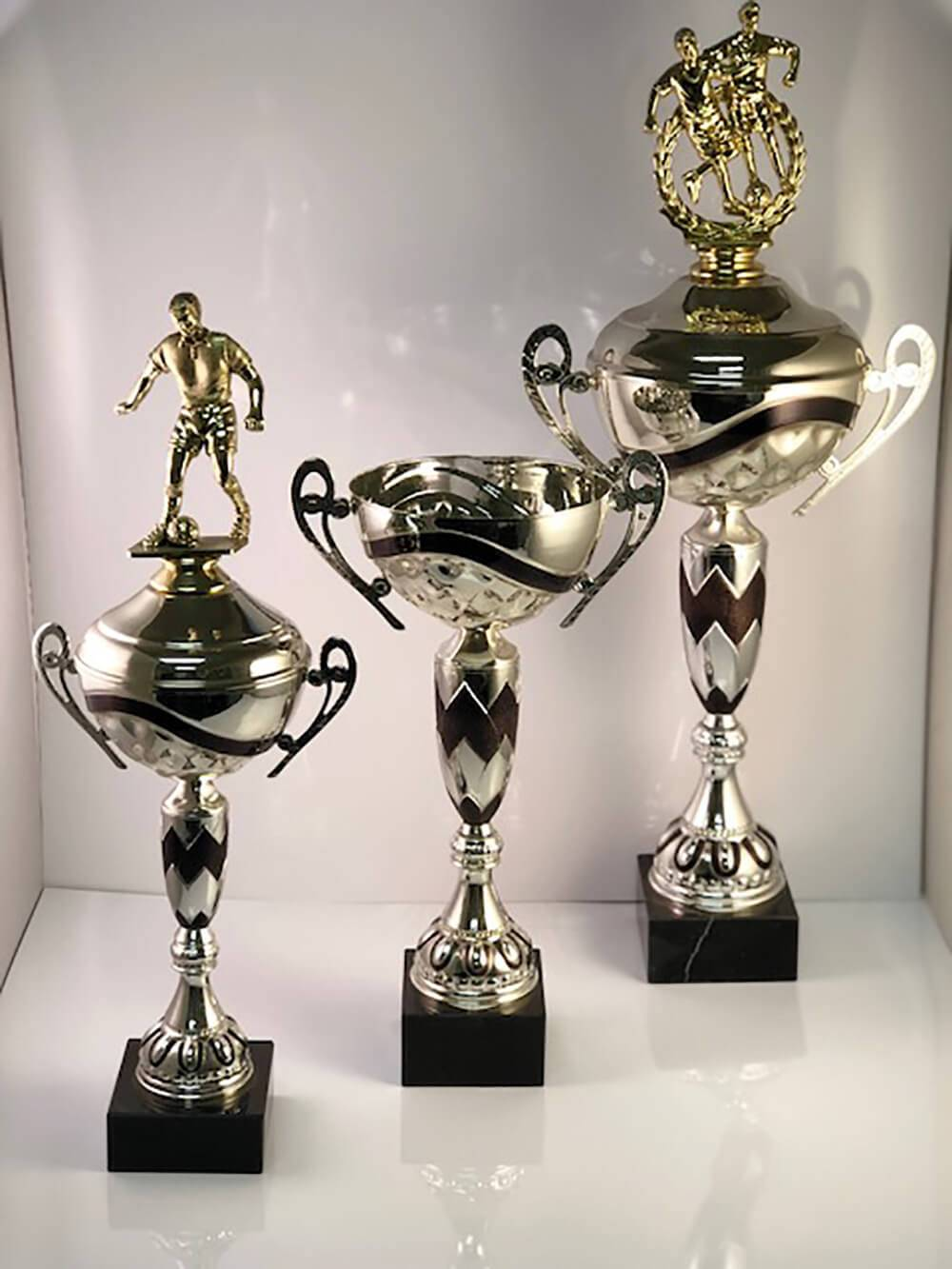 Examples of different statuette cup trophies available for customization at APS.