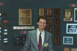 Joel Fertig poses in front of an APS Awards booth.