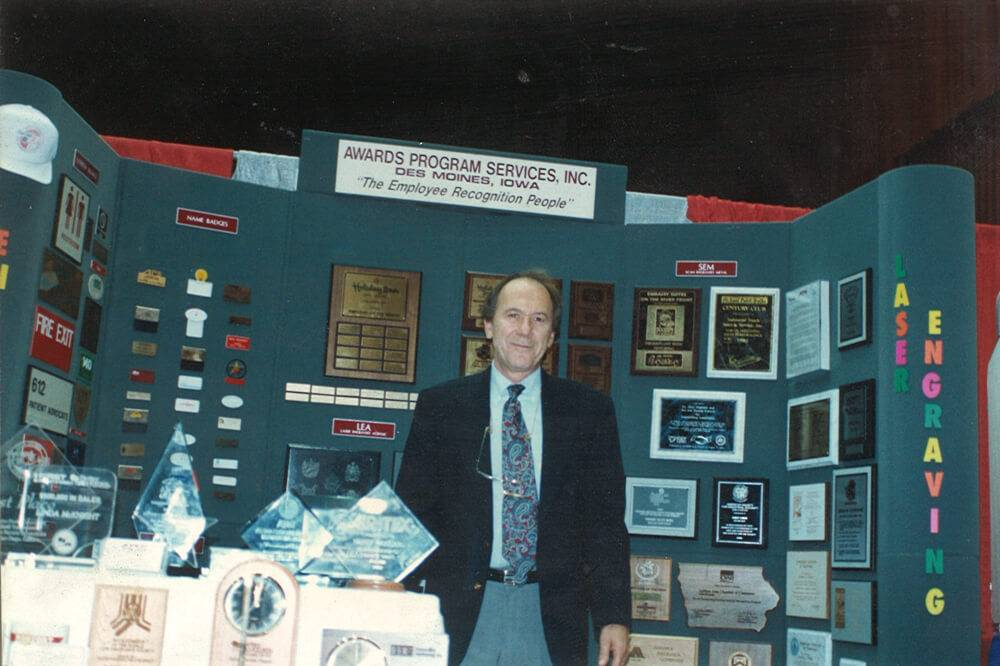 Dave Fertig poses in front of an APS Awards booth at a convention.