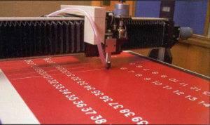 APS engraves numbers onto a vinyl board.
