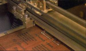 A wooden plaque is engraved by APS machinery.