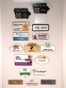 An assortment of different types of name badges made by APS.