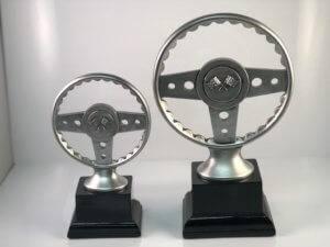 Two silver racing trophies in the shape of steering wheels.